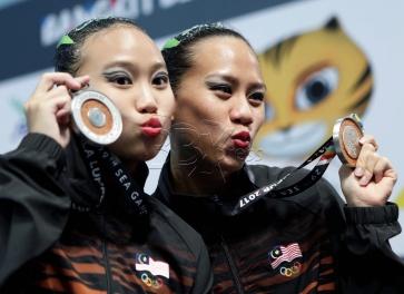 Atlet Malaysia, Lee Yhing Huey (kanan) dan Gan Hua Wei merangkul pingat perak acara renang berirama dalam rutin Duet Teknikal di pusat Akuatik Nasional Bukit Jalil, KL Sport City Sukan SEA Kuala Lumpur 2017. NSTP/AIZUDDIN SAAD